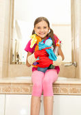 Smiling girl posing with cleansers in bottles at bathroom — Stock Photo