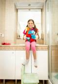 Girl helping with cleaning bathroom posing with cleansers — Stock Photo
