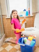 Smiling girl cleaning toilet with brush — Stock Photo