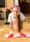 Portrait of smiling teenage girl washing floor with cloth — Stock Photo