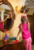Girl with pigtails cleaning lamp with feather brush — Stock Photo