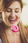 Toned portrait of cute funny woman licking her lips at lollipop — Stock Photo