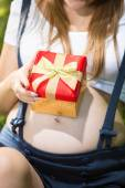 Closeup of pregnant woman holding red gift box on big abdomen — Stock Photo