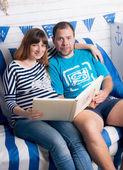ソファーに座っていると、フォト アルバムを見て期待して赤ちゃんカップル — ストック写真