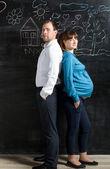 Mari et femme enceinte pose contre un mur noir avec dessin — Photo