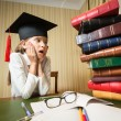 Girl in graduation cap looking at high heap of books on table at — Stock Photo #80184196