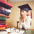 Amazed smart girl in graduation cap looking at big heap of books — Stock Photo #80184204
