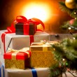 Stack of gift boxes under Christmas tree at fireplace — Stock Photo #83863054