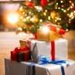 Gift boxes under Christmas tree next to fireplace at living room — Stock Photo #83863346