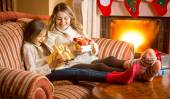Mother and daughter unpacking Christmas presents next to firepla — Stock Photo