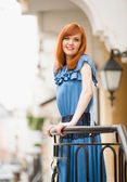 Beautiful smiling redhead girl in blue dress posing on street — Stock Photo