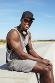 Happy young african man sitting on a promenade — Stock Photo