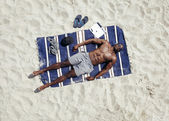 Young guy lying shirtless on a mat sunbathing — Stock Photo