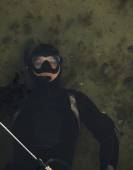 Spearfishing diver showing thumbs sign while in water — Stock Photo