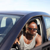 Afro american guy sitting in his car — Stock Photo