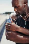 African muscular athlete listening to music — Stock Photo