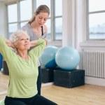 Постер, плакат: Trainer helping senior woman exercising