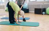 Elder woman exercising with help from trainer — Stock Photo