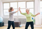 Senior woman giving high five to her coach at gym — Stock Photo