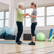 Постер, плакат: Trainer helping senior woman exercising with a bosu balance