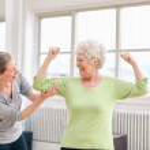 Постер, плакат: Proud elderly woman flexing her bicep with personal trainer
