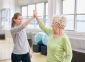 Senior woman rejoicing health success with her trainer at rehab — Stock Photo