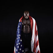 Male athlete carrying an American flag — Stok fotoğraf