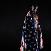Male athlete carrying an American flag — Stock Photo