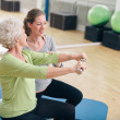 Постер, плакат: Senior woman assisted by personal trainer in gym