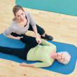 Physical therapist helping senior woman do leg stretches — Stock Photo #60331169