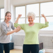 Fit senior woman showing her biceps at gym — Stock Photo #61552259