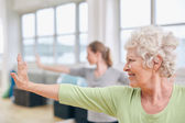 Senior woman doing stretching exercise at yoga class — Stock Photo