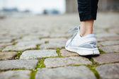 Leg of female jogger walking on pavement — Foto de Stock