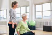 Female instructor assisting senior woman exercising in gym — Stock Photo