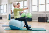 Female trainer assisting senior woman lifting weights — Stock Photo