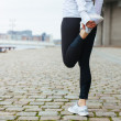 Fit young woman stretching her leg before a run — Stock Photo #63314141