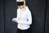 Woman taking a break form workout using mobile phone — Stock Photo