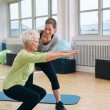 Elderly woman doing exercise with her personal trainer — Stock Photo #63863845