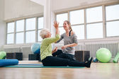 Happy elder woman rejoicing health success with her trainer — Stock Photo