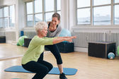 Elderly woman doing exercise with her personal trainer — Zdjęcie stockowe
