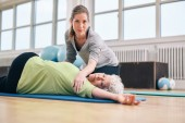 Trainer helping senior woman in her stretching workout — Stok fotoğraf