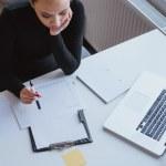 Woman analyzing chart of work progress and planning — Stock Photo #64604141