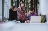Young team of designers discussing magazine publication — Stock Photo