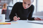 Young woman at her desk taking note — Stock Photo