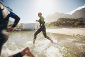 Participants running into the water for start of a triathlon — Stock Photo