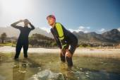 Determined athletes in wet suits preparing for triathlon — ストック写真