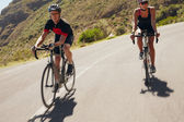 Man and woman cyclist riding down the country road — Foto de Stock