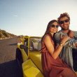 Attractive young couple sitting on the hood of their car — Stock Photo #71488803