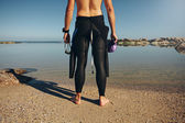 Young man standing on lake wearing wetsuit — Stock Photo