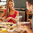 Happy young couple having breakfast at home — Stock Photo #73197595